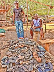 Young men selling used  Broni-wewu shoes in a market the town of Tamale, northern Ghana