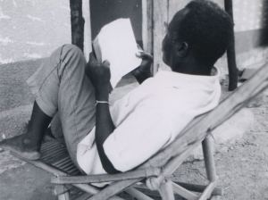 Paul Hema reads the Bible in front of his humble dwelling in Burkina Faso