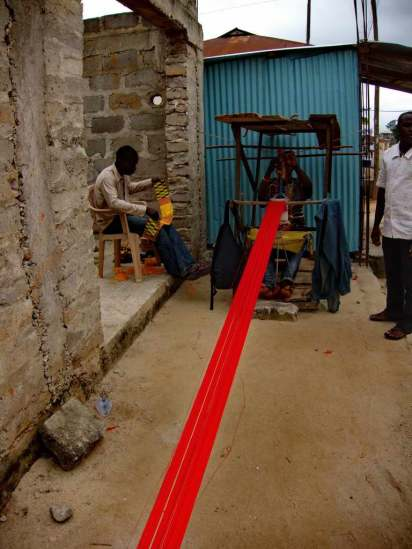 Long line of thread stretching out from the loom. On the other end, it is secured by a heavy object, often a large rock.