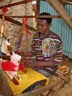 Young man weaving Kente cloth