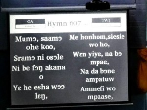 Singing hymns in two Ghanaian languages as the same time. This was at a business meeting conducted in English.