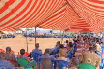 Event guests in their plastic chairs under canvas awnings