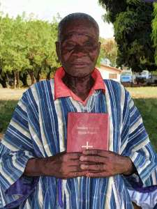 Nawuri man with the New Testament in his language, Ghana