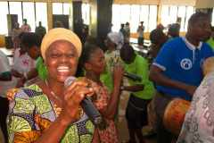 A woman leads a worship song in a local language during a gathering of believers from northern Ghana in a city in the south