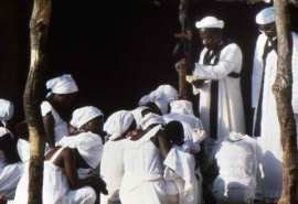 Pastor of a Harrist church prays for members of the congregation