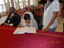 The bride signs the official wedding register for the clerk (the groom signed too).